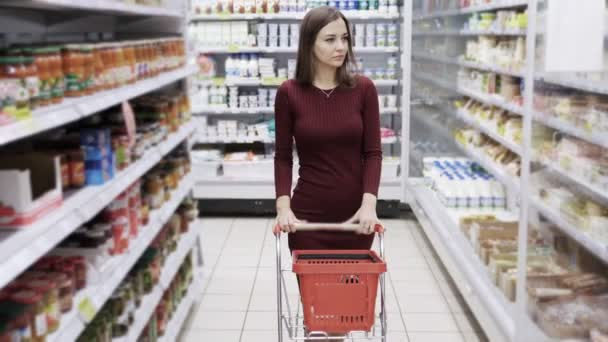 Attractive woman shopping at supermarket, steadicam shot