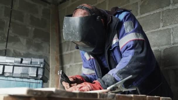 Boční pohled svářečka svářecí maska svary dvě kovové části. Dělník v kombinéze pracuje uvnitř