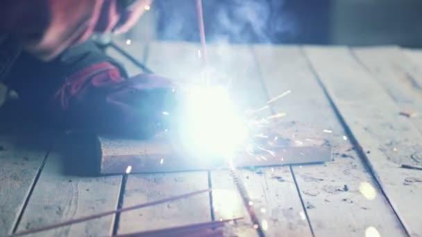 Detail, svářeč svařuje dvě kovové části. Dělník v kombinéze pracuje uvnitř, pomalý pohyb