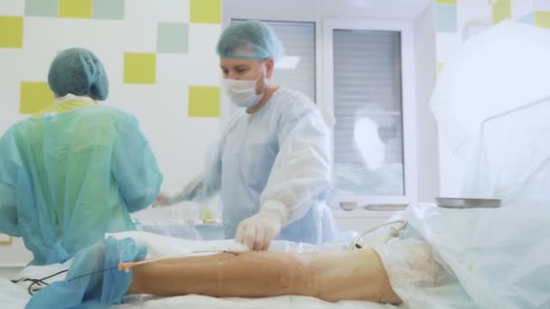 Surgeon in sterile clothes punctures leg of patient during sclerotherapy operation.