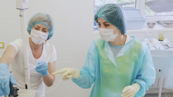 Nurses in sterile clothes prepare medical equipment before surgery.
