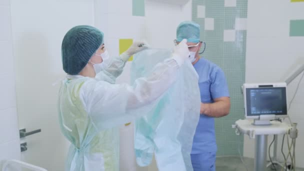 Nurses help the doctor to put on sterile clothing in operating room before surgery