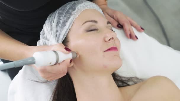 Nahaufnahme Kosmetikerin Hände macht Anti-Aging-und Lifting-Verfahren auf Gesicht junge Frau in der Klinik