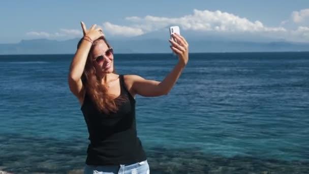 Happy girl traveler in sunglasses makes selfie on phone, ocean on background