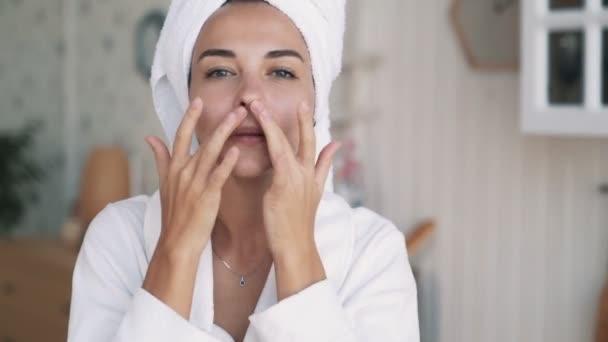 Nahaufnahme von Mädchen im Bademantel, mit Handtuch auf dem Kopf macht verjüngende Gesichtsmassage