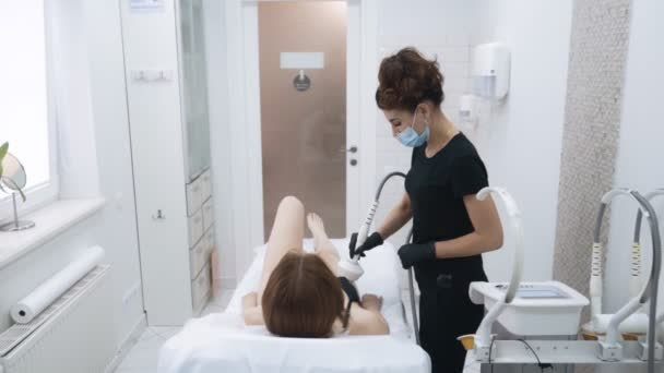 Beautician does skin tightening procedure on patient body at clinic, slow motion