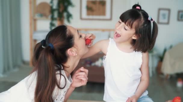 Mladá matka a roztomilá dcerka jíst jahody, zpomalený film