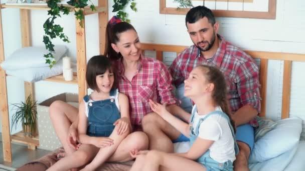 Genitori felici e due figlie si divertono insieme a casa, si siedano a letto