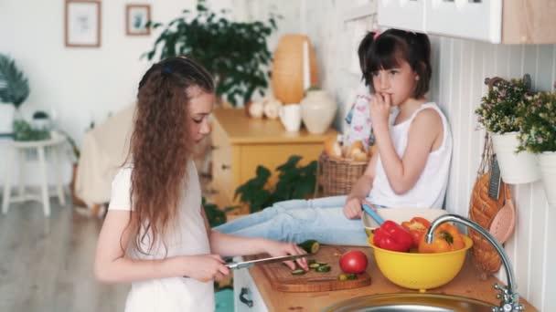 Kislány darabok uborka konyhaszekrény, a húga ül az asztalon, lassú mozgás