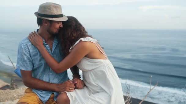 Lovers sit in romantic place, hug, beautiful view on background, slow motion