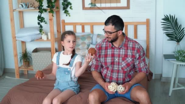 Dad And Daughter Sit On Bed And Try To Juggle With Balls Slow