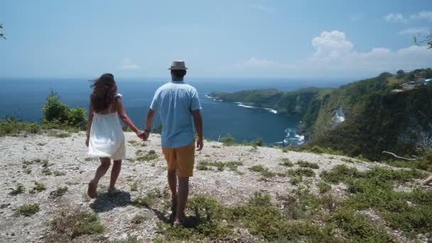 Couple of lovers hand in hand go to cliff look at view of ocean, slow motion