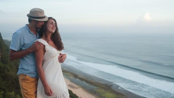 Párek milenců, objetí, líbání a flirtování na pozadí oceánu, pomalý pohyb
