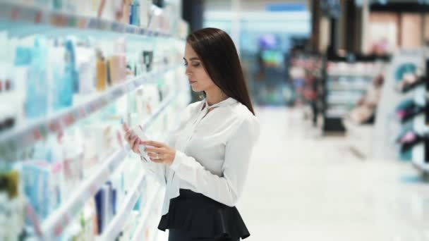 Pretty girl in cosmetics shop chooses cream, looks at goods, reads ingredients