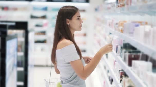 Fiatal nő választja parfüm kozmetikai bolt és szippantás is, lassított