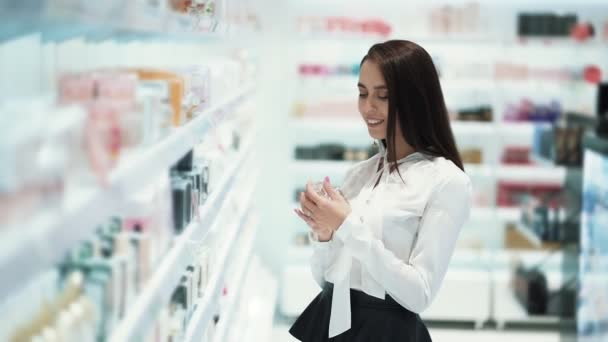 Woman chooses perfume in cosmetics shop, sprays it on tester and sniffs it