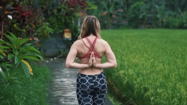 Rückansicht junge Frau macht Yoga-Übungen im Freien, Grün im Hintergrund