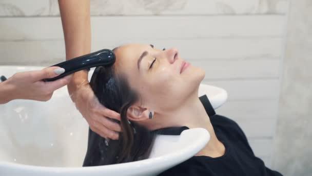 Közelről fodrászat mossa haját a nő a szépségszalonban, lassított