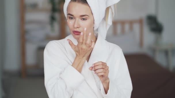 Nő törülközővel a fej vonatkozik hidratáló krém az arcán, közelről