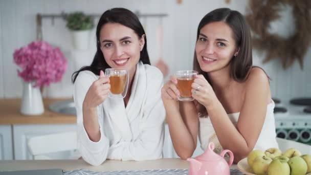 zwei schöne Mädchen trinken morgens Tee in der Küche und schauen in die Kamera