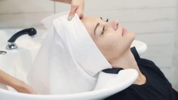 Kadeřník balení žena vlasy v bílém ručníku po mytí, zpomalený pohyb