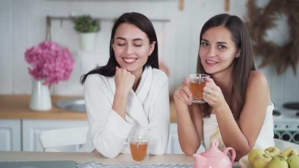 Dvě krásné dívky pít čaj v kuchyni v dopoledních hodinách a podívejte se na kameru