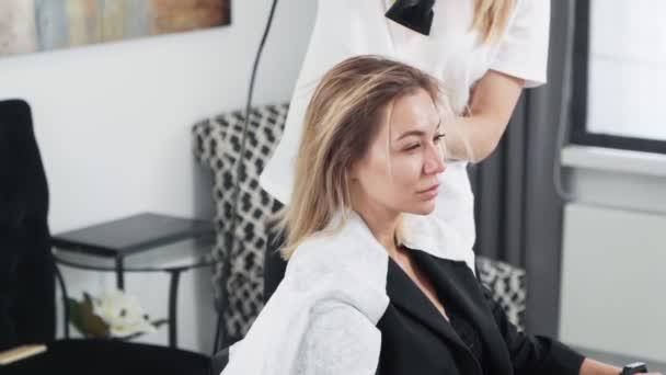 zblízka, kadeřnice vysuší žena mokré vlasy s kulatým hřebenem, zpomalený pohyb