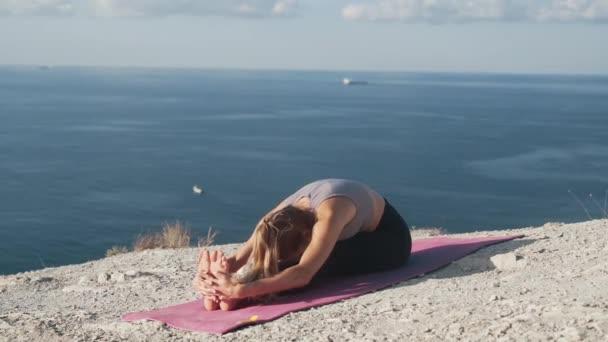 Frau macht morgens Übungen und dehnt sich mit Blick aufs Meer, Zeitlupe