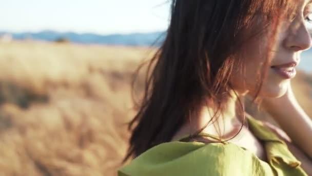 Portrét usměvavé ženy ve zlatě slunečních paprdech, vítr jí fouká vlasy, pomalý pohyb