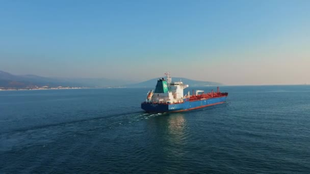 Letecký pohled po ultra velké nákladní lodi na moři opouští přístav za slunečného dne