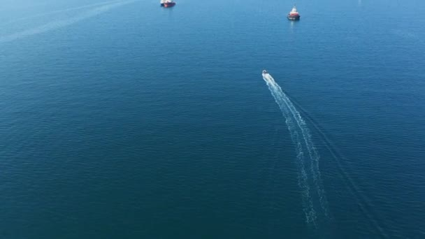 Aerial view of small boat sails on blue sea among larger vessels