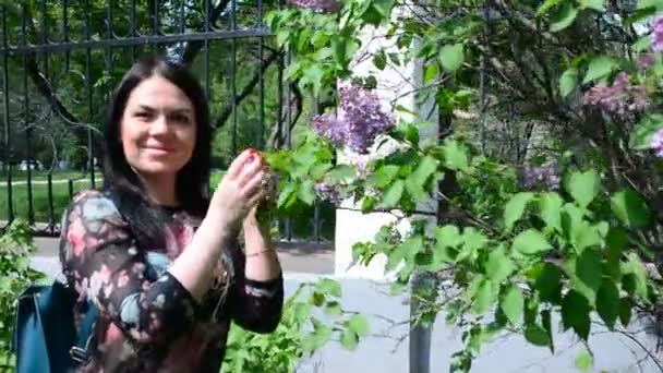 beautiful woman walks in the park among the lilac