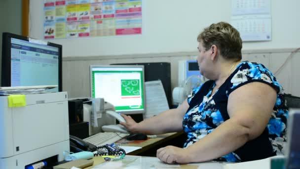 In der Schaltzentrale der Aufzugswartung redet eine Mitarbeiterin weiter. Es gibt mehrere Monitore und ein Telefon.