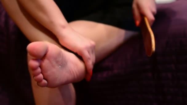 Mädchen kümmern sich um Beine Pediküre, waschen Sie Ihre Füße. Pediküre zu Hause. Die kümmert sich um die Nägel, tun die Pediküre. Peeling Füße Pediküre Verfahren.