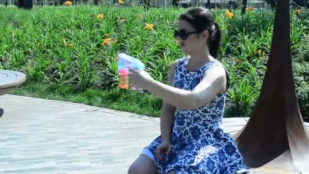 Cute girl have fun with soap bubbles. Young beautiful woman plays with bubbles in park.