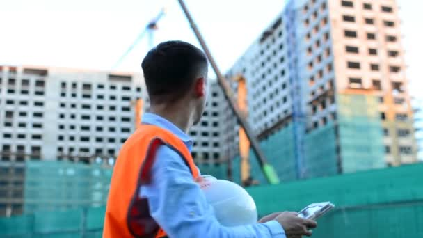 Adult engineer or architect uses a tablet in operation. Writes a message or checks a drawing. Against background is building. Builders are building a modern residential building of glass and concrete.