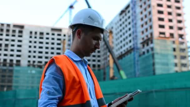 Pro dospělé inženýr nebo architekt používá tablet v provozu. Zapíše zprávu nebo odevzdá výkres. Pozadí je budova. Stavitelé jsou budování moderní bytový dům ze skla a betonu.