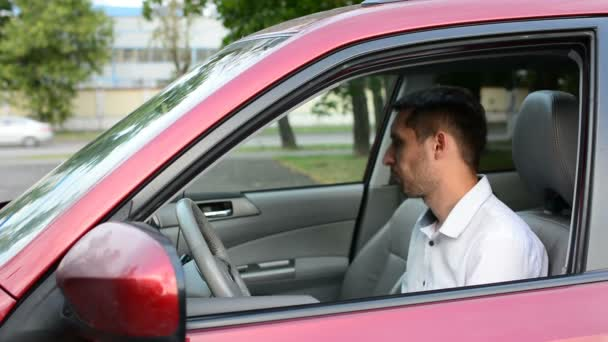 Young driver being impatient, waiting inside his car and showing signs of frustration.