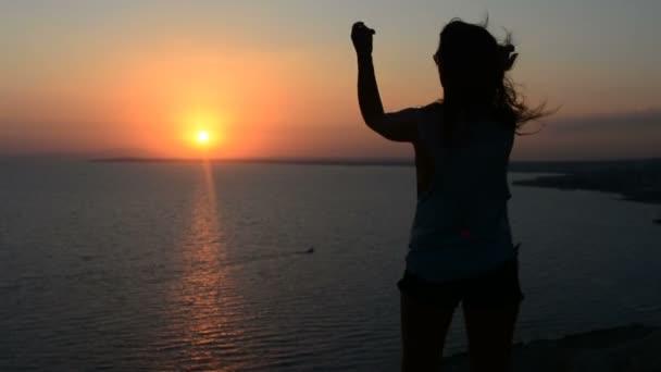 Siluetta di giovane donna attiva che ballano allaperto su un tramonto con il sole splende luminoso dietro di lei un orizzonte.