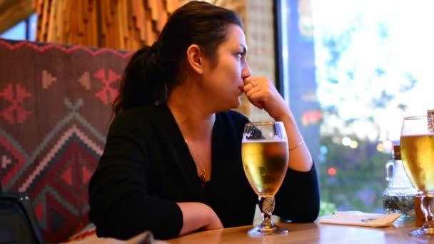Ein Mädchen trinkt Bier aus einem Glas. Bier im Glas steht auf dem Tisch. Eine Bierkneipe ist ein Restaurant.