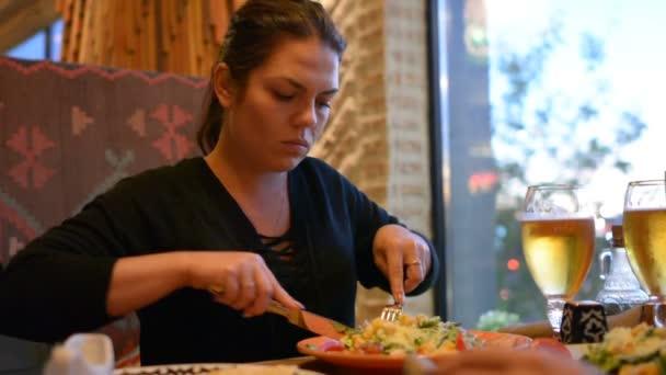 Portrét atraktivní bruneta žena jíst těstoviny v kavárně. Hladová dívka cítí šťastný po večeři.