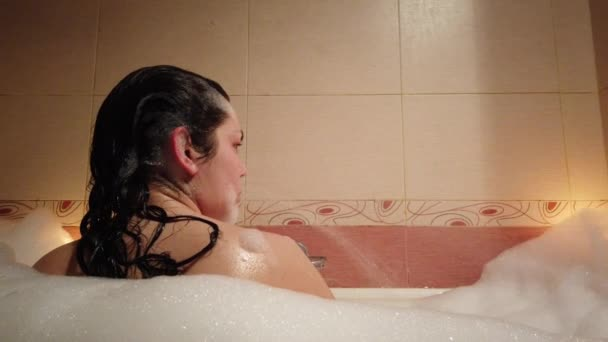 Atraktivní mladá žena ve vaně bublina hořením svíčky