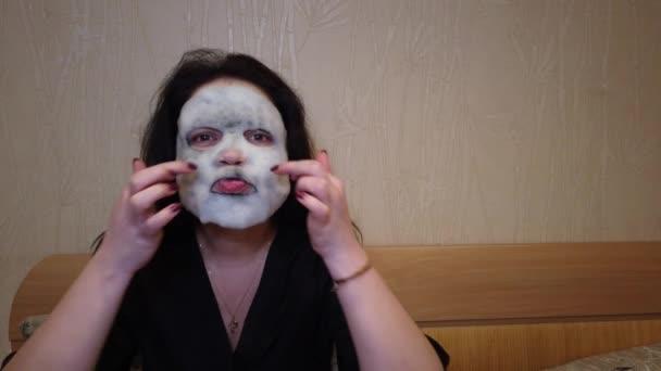 Frau trägt abends Papiermaske auf Gesicht auf Bett auf