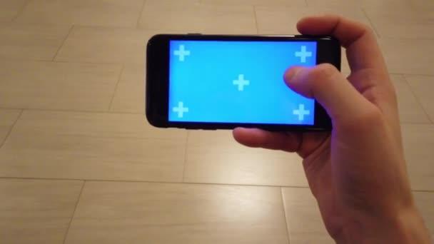 Young Man sta tenendo smartphone. Utilizzando touchscreen touch, toccare, scorrere i gesti della mano sullo schermo blu.