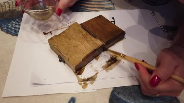 Woman painting wooden box with a brush in brown color