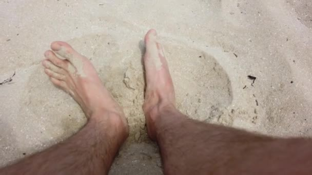 Feet of a human are rummaging sand on the beach in the summer in warm weather. Sandy shore. Rest on the sea.
