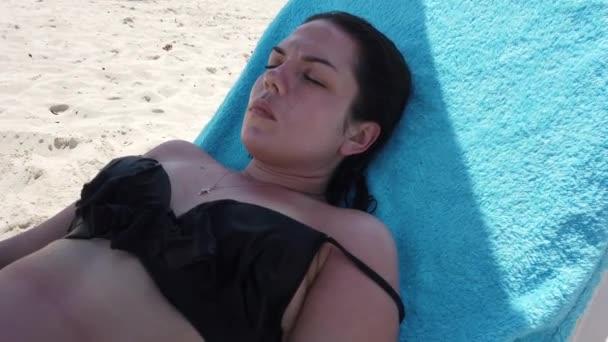 Nyaralás strand utazás napbarnító fiatal nő a pihentető tengerparton bikini. Napozó gyönyörű lány feküdt nyugágyon a luxus szálloda Resort. Paradise strand.