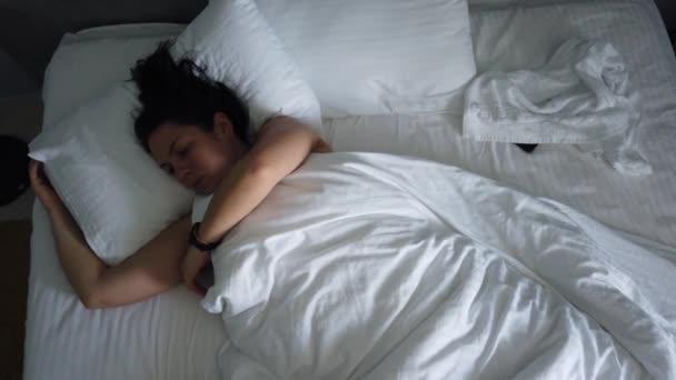 Top-Ansicht junge Frau, die im Bett unter Decke aufwacht. Nettes Mädchen überprüft ihr Smartphone erste Sache am Morgen.