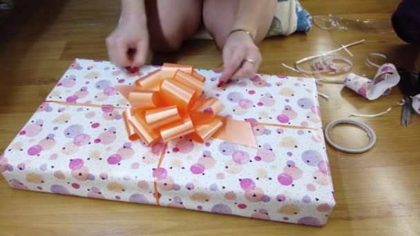 The girl packs fires in beautiful multicolored paper and ties with an orange bow.