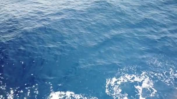 Vodní cesta na modrém mořském povrchu z plovoucí lodi. Trail tyrkysová mořská voda s pěnou a vlnami, rozlití, bubliny, stopy z lodi.